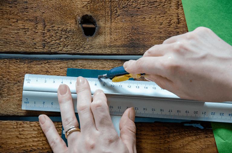 Schneide mit einem Cuttermesser und einem Lineal ein Fenster in deine Streichholzschachtel