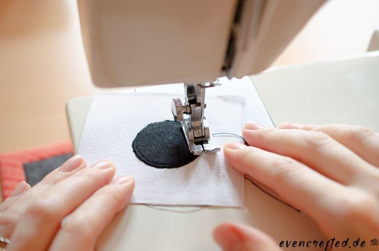 Schwarzen Stoffkreis auf ein rechteckiges weißes Stoffstück aufnähen und hinter die Augenlöcher im Frottee legen